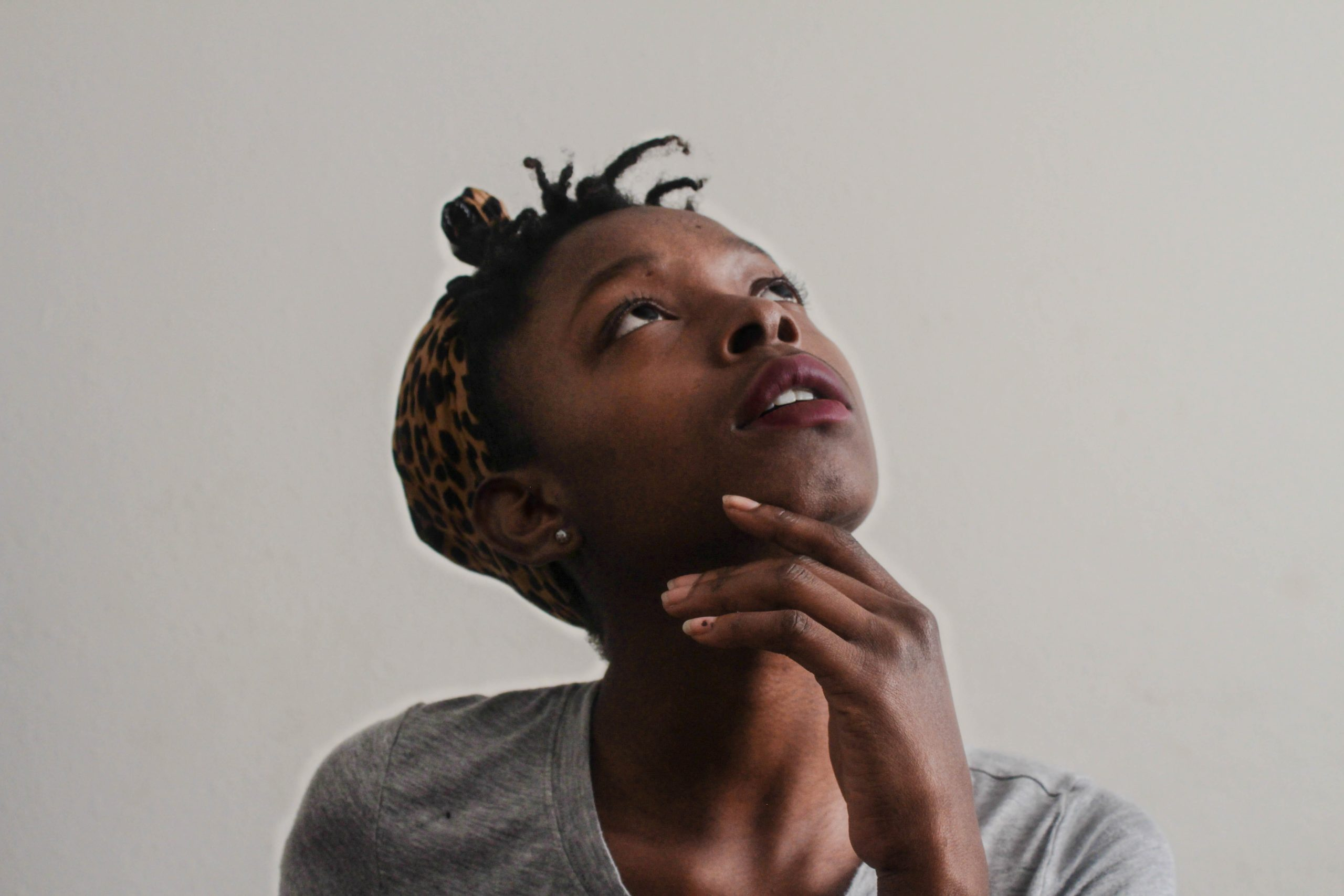 African American girl in a gray shirt looking upward in a thinking postion.