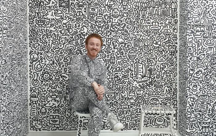 Sam Cox (AKA Mr. Doodle) posing in front of his art in Korea.