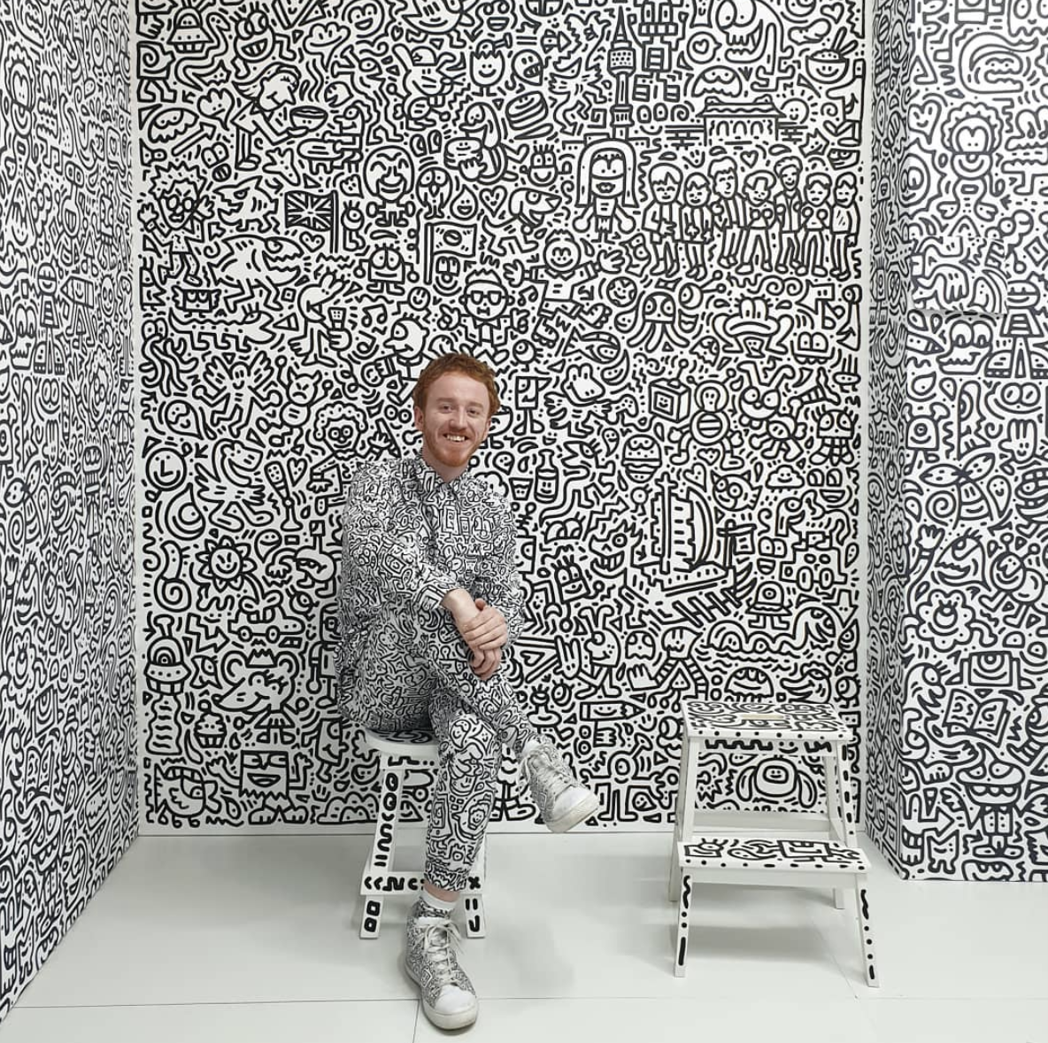 Sam Cox (AKA Mr. Doodle) posing in front of his art in Korea.